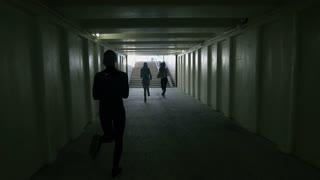 Three girls run along the tunnel.