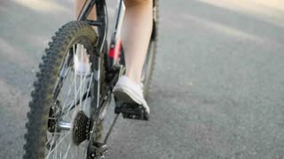 Urban biking - woman riding bike in city park.