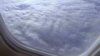 view of the clouds through the glass of the porthole of a flying airplane.
