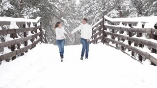 Winter fun couple playful together during winter holidays vacation outside in snow forest.