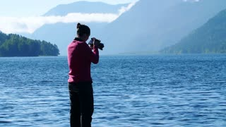 Young woman taking photo of mountain. woman photographer taking photo at the lake.