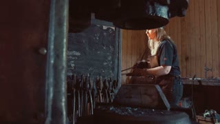 Woman blacksmith forges a horseshoe.