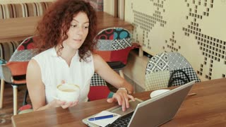 woman in a cafe , drinking coffee and working on the laptop .