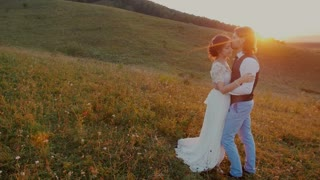 Young couple embracing and whirling at sunset .