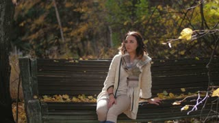 young girl sitting on a bench in the autumn wind