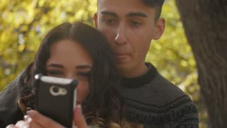 young man and woman sitting on a bench in autumn look in the phone