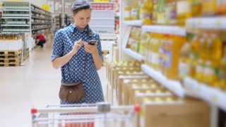 Young woman buys sunflower oil in supermarket