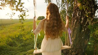 Young woman on a swing in the summer evening.
