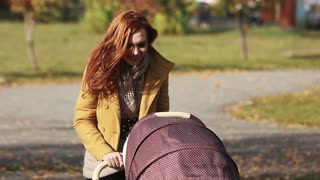 A young mother with a baby carriage walking in a park