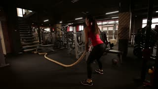 An attractive young and athletic girl using training ropes in a gym.