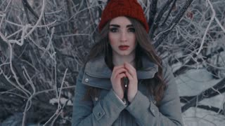 beautiful girl freezing in winter park. cold winter. portrait girl in a red cap and jacket warms her hands. Closeup portrait of beautiful young girl in winter day