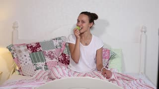 Beautiful woman giving bite to green apple