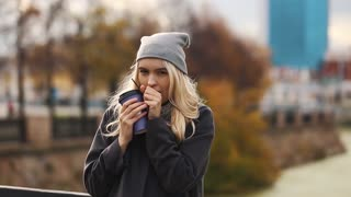 Beautiful young woman with a cup of coffee in the autumn city. Warmed by hot coffee.