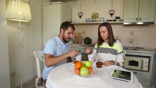 Couple eating breakfast muffins with coffee