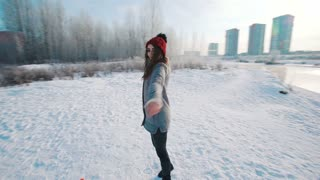 Girl in red hat and scarf walking in winter park near river. She is smiling and very pleased and happy.