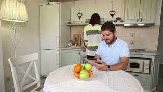 Girl preparing food while man looking at tablet (eBook) in home kitchen