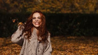 Happiness carefree leisure concept. Redhaired long hair woman relaxing in autumn park throwing leaves up in the air. Beautiful girl in orange forest foliage outdoor.