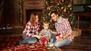happy family with a little boy in the Christmas and New Year tree looking at the camera and smiling 2017