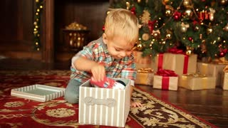 Little boy under the Christmas tree for Christmas and New Year 2017