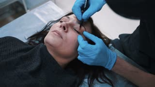 plastic surgeon checking middle aged woman face before cosmetic surgery