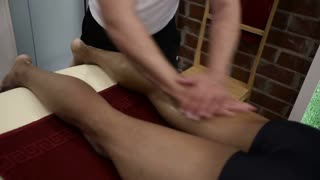 Sports massage - Leg massage - Physical therapist doing massage of calfs, applying strong finger pressure. Toned image, selective focus.