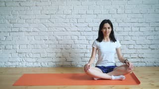 A beautiful, intelligent, athletic girl does yoga exercises in the gym in an attic style, with natural lighting of large windows. Against the background a white brick wall for the logo.