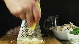 A chef rubs parmesan cheese.