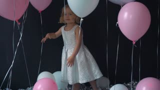 A portrait of a beautiful little girl smiles and holds in a hands color balloon in the studio with many balloons and a toy candy shop.