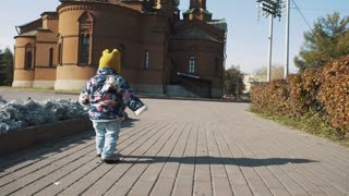 A small child is walking alone in an autumn park
