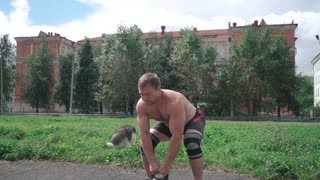 A strong man, crossfit, taking the kettlebells with both hands and tossing it in slow motion