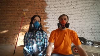 A young couple moves into a new home. Wife and husband sit in respirators. Tired after the working day.