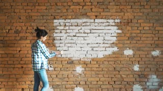 A young girl paints a brick wall in her house with a roller. Painting walls with a roller. Paint the bare walls with a roller of white paint.