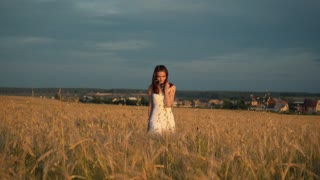 a young girl stands in a Golden field of wheat at sunset and raises his hands up, slow motion