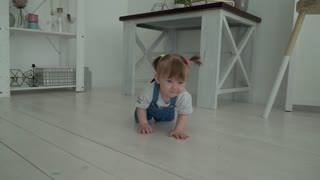 Adorable smiling baby crawling on floor towards the camera