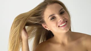 Attractive smiling women portrait with long blond hear looking to the camera on white background