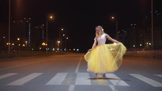Beautiful ballerina dancing on a city street.