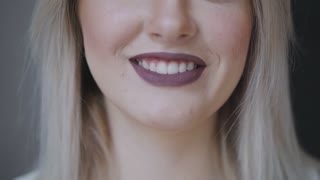 Beautiful female face. Perfect toothy smile. Caucasian young girl close-up portrait. Dark lips, skin, teeth. Isolated on grey background. Studio shot . happy positive girl