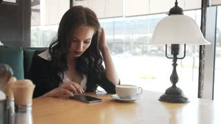 Beautiful girl drinking coffee at the cafe with smartphone. Young business lady works in a comfortable modern cafe. Beautiful working woman work outdoor. Business Concept.