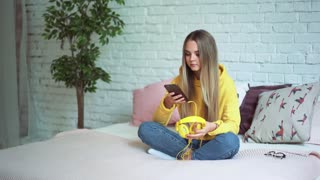 Beautiful girl listening to music on headphones on the bed and relaxing using the phone