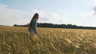 Beautiful girl running on sunlit wheat field. Slow motion 120 fps. Sun lens flare. Freedom concept. Happy woman having fun outdoors in a wheat field on sunset or sunrise. Slow motion. Harvest.