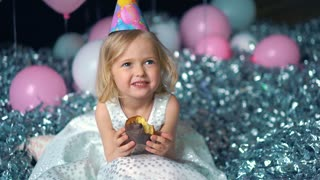 Beautiful happy little girl biting birthday cake. Looking at camera.