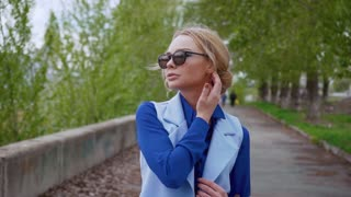 Beautiful sexy blond business women wearing sunglasses blue suit waiting for meeting in the city at the river relax enjoying