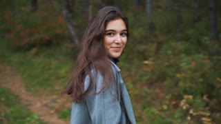 beautiful young brunette girl walking in the Park in autumn.