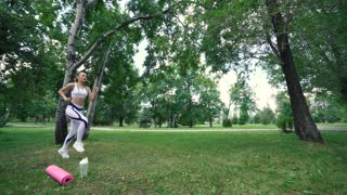 beautiful young model girl training runs in the Park, slow motion
