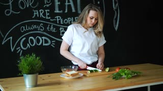 Beautiful young woman cuts green cucumber with kitchen knife on round pieces on wooden cutting board and prepares healthy fresh salad, next to it there green lettuce leaves and tomato with cucumber on