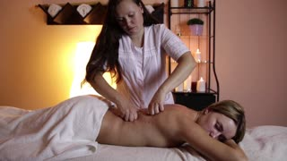Beautiful young woman getting back massage in spa.
