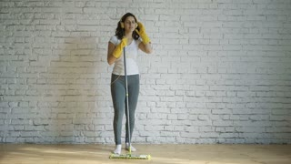 Beautiful young woman in protective gloves is singing using a mop and dancing while cleaning her house in living room during end of year clean