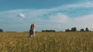 Beautiful young woman running across the wheat field looking around.