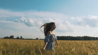 Beauty brunette girl with healthy long hair spinning and laughing outdoor on golden wheat field. Enjoying nature. Young woman in dress having fun outdoor. Sunset.