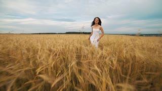 Beauty Girl Outdoors enjoying nature. Beautiful Teenage Model girl in white dress running on the Spring Field, Sun Light. Glow Sun. Free Happy Woman. Toned in warm colors